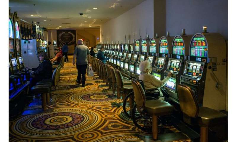 A woman plays the slot machine in a near empty casino in Atlantic City, where the closure of some casinos in recent years contri
