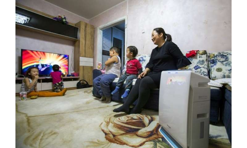 Batbayariin Munguntuul sitting with her children while an air purifier runs at her home in Ulaanbaatar