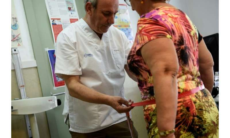 Carlos Pineiro (L), a 63-year-old family doctor, is behind a programme for residents in the small Spanish town of Naron to lose