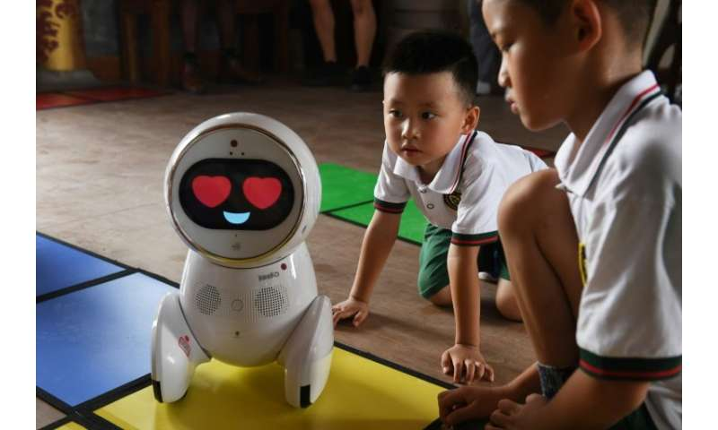 Children watch a Keeko robot at the Yiswind Institute of Multicultural Education in Beijing, where the intelligent machines are