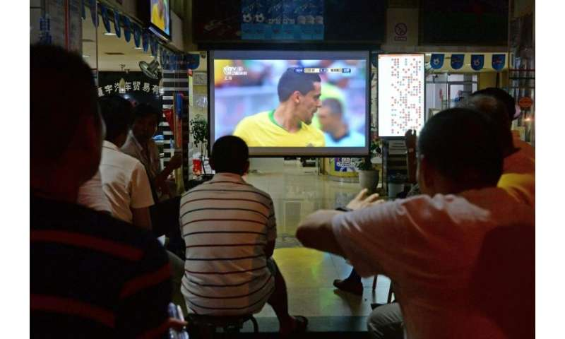Fans watch the 2018 Russia World Cup round of 16 football match between Brazil and Mexico at a China Sports Lottery outlet in Sh