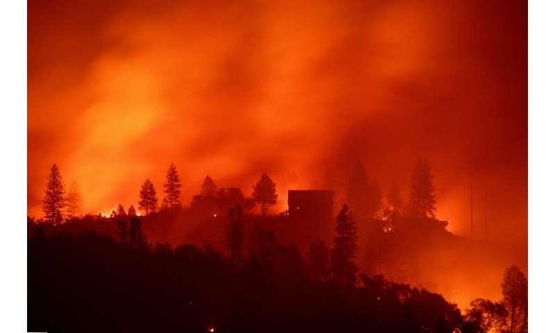 Flames from the Camp Fire burn near a home atop a ridge near Big Bend, California