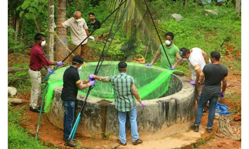 Indian authorities inspect a well to to catch bats suspected of carrying the Nipah virus