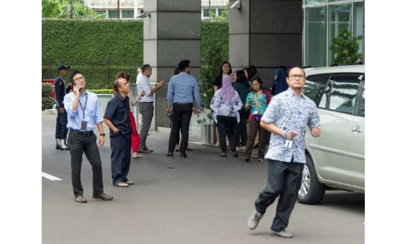 Indonesians stand outside office buildings after a strong quake hit Jakarta