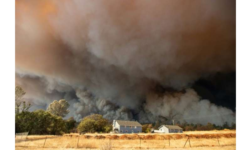 In this photo taken on November 8, 2018 a home is overshadowed by towering smoke plumes as the Camp fire races through town in P