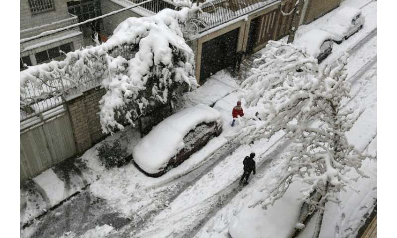 Iranians walk in the snow in the capital Tehran on January 28, 2018
