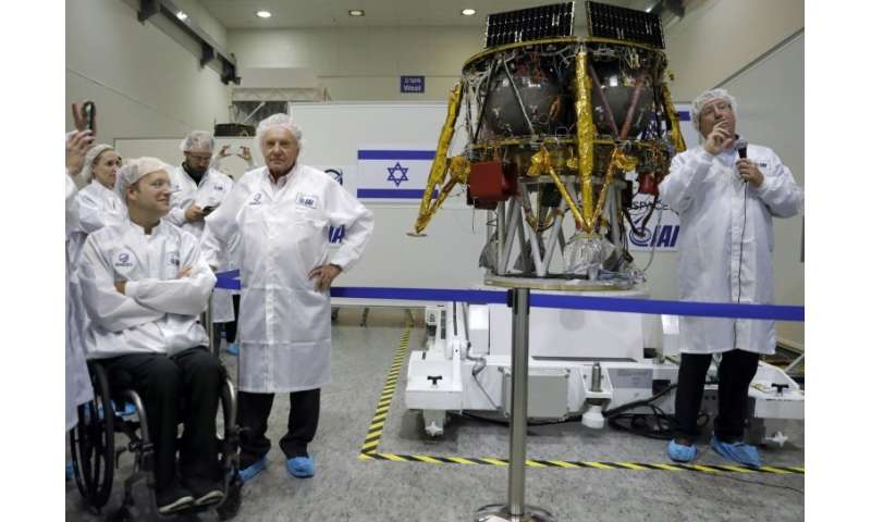 Israeli Aerospace Industries director of Space division Opher Doron (R) and billionaire investor Morris Kahn (2nd-R) present a s