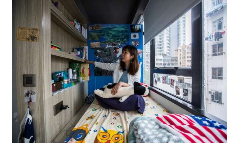 Jezz Ng in a small living space in a co-sharing building in Hong Kong, where box-like 'nano-flats' and co-shares have been toute