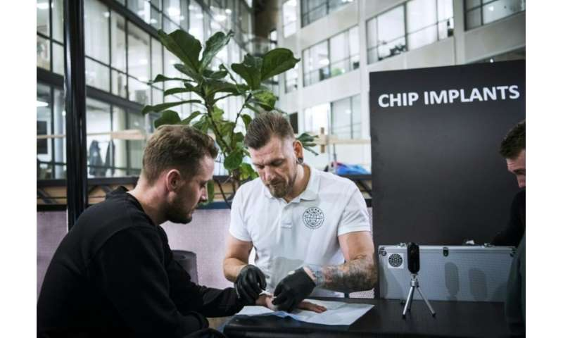 Jowan Osterlund (R), a piercings specialist and self-proclaimed champion of chip implantation, brushes off fears of data misuse