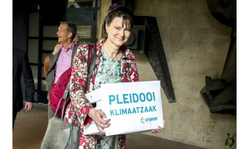 Marjan Minnesma, director of environmental group Urgenda, carries a box saying 'climate case appeal' outside court in The Hague