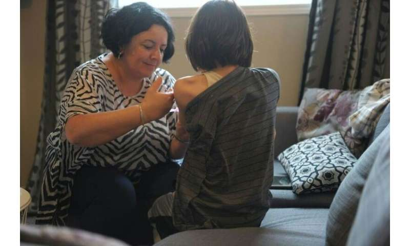 Melanie Ferrer helps her son Julien with one of the three injections he needs per week to treat his condition