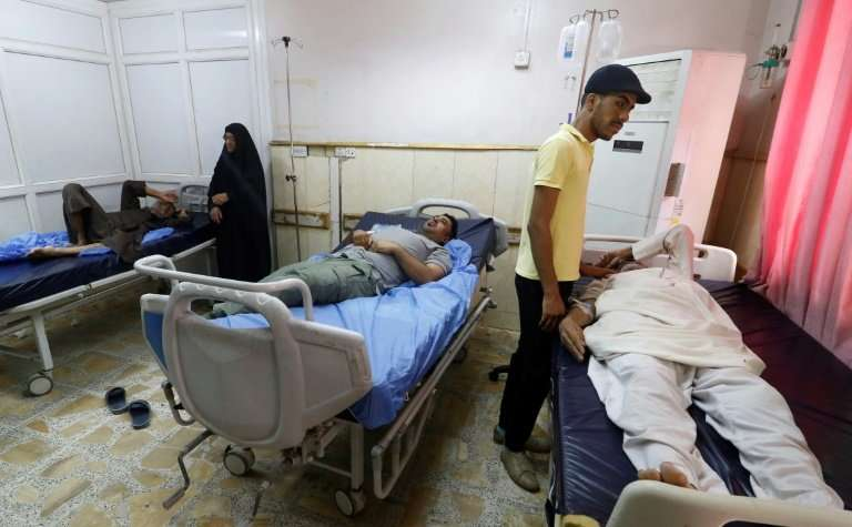 Men lie at a hospital in Basra in southern Iraq, on August 29, 2018, after falling ill from drinking polluted tap water