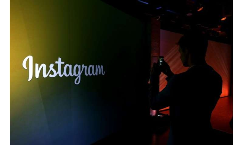 MENLO PARK, CA : An attendee takes a photo of the instagram logo during a press event at Facebook headquarters on June 20, 2013