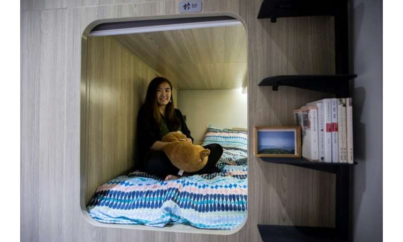 Michelle Chau sits on her bed in a co-sharing building in the Mong Kok district of Hong Kong, where spiralling housing prices ha