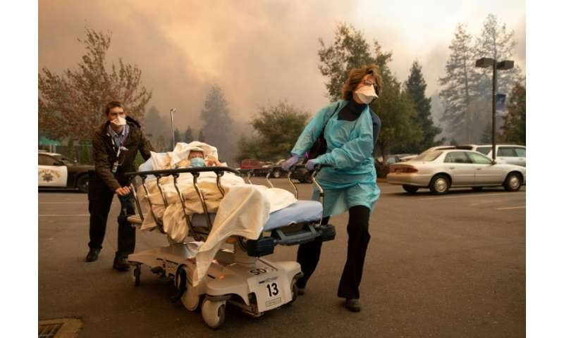 Patients are quickly evacuated from the Feather River Hospital as it burns down during the Camp fire in Paradise, California on