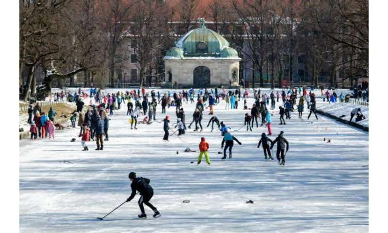 People play ice hockey on the frozen canal at Nymphenburg Palace in Munich, southern Germany on Sunday