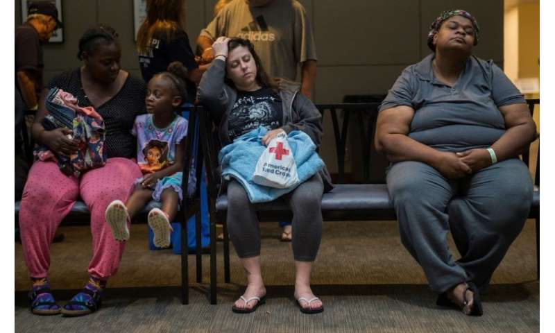 People rest at a Red Cross shelter near Raleigh, North Carolina, while waiting to take a shower, on September 17, 2018