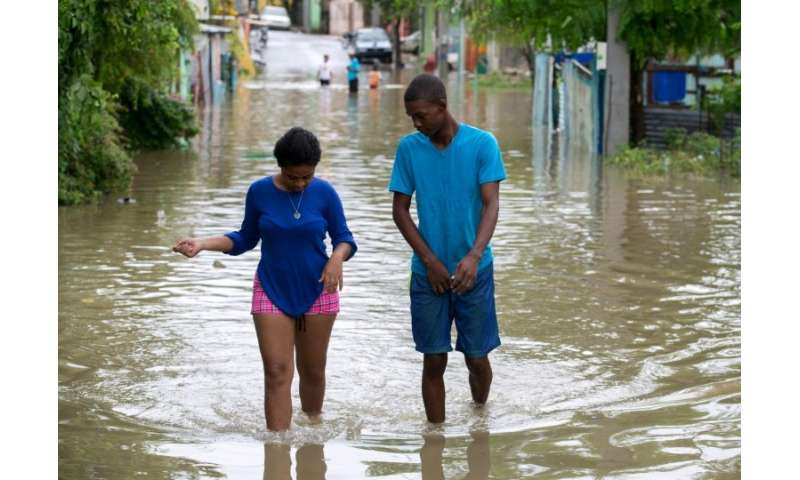 People wade through water in the flooded Moscu neighbourhood, in San Cristobal, Dominican Republic, after heavy downpours from t