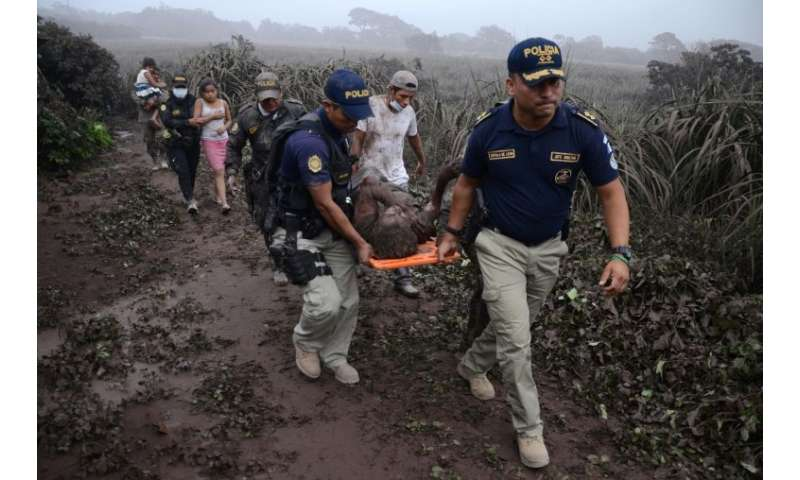 Police officers carry a man injured by the eruption of Guatemala's Fuego volcano
