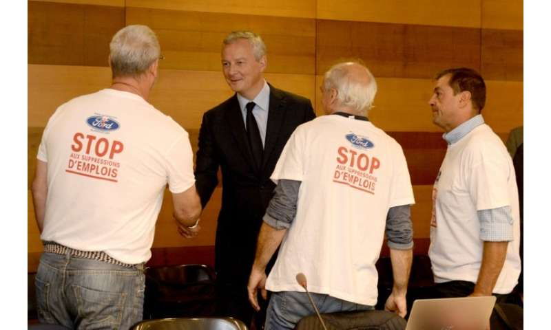 """Stop job cuts"" read the T-shirts of trade unionists greeting French Economy and Finance Minister Bruno Le Maire at a"