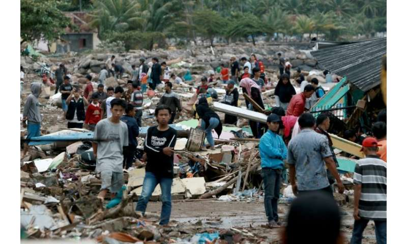 Rescuers and residents look for survivors after a volcano-triggered tsunami left at least 222 people dead