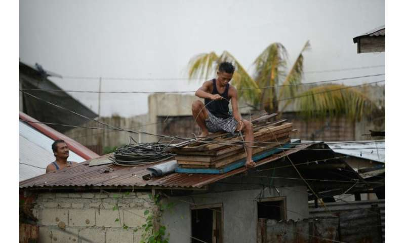 Residents secure the roof of their house as Typhoon Mangkhut approaches the city of Tuguegarao, Philippines