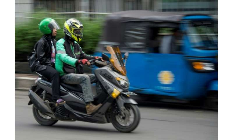 Ride-hailing apps like the Grab motorcyle-taxi seen here are denting the fortunes of traditional three-wheeled bajaj taxis in In