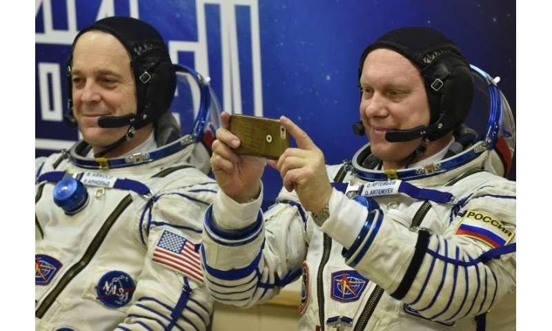 Roscosmos cosmonaut Oleg Artemyev takes a last-minute snap, alongside NASA astronaut Richard Arnold, before they headed into spa