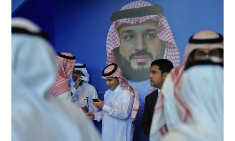 "Saudi men chat in front of a poster of Saudi Crown Prince Mohammed bin Salman during the 2017 ""MiSK Global Forum,"" par"