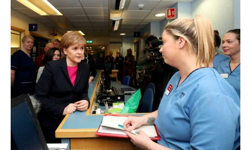Sturgeon (L) meets clinicians during a visit to the Edinburgh Royal Infirmary as she marks the minimum unit pricing for alcohol