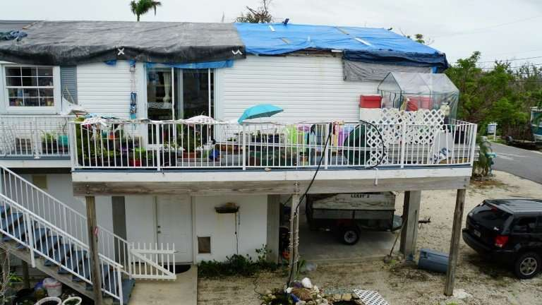 Tarps cover a house with the roof still unrepaired after the damage caused by hurricane Irma in Big Pine Key, Florida