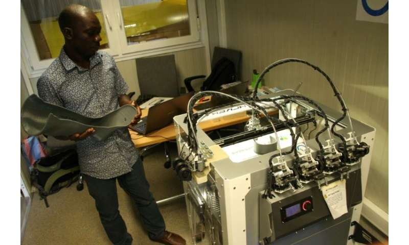Technician Fabrice Agbelehounko Djodji checks the work of a 3D printer used to produce prosthetic supports at the African Organi