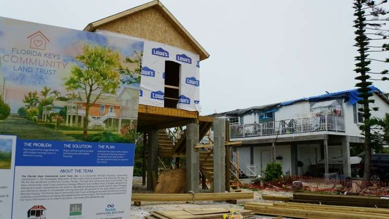 The model of an affordable house built to withstand storms, is seen next to a house with the roof still unrepaired and covered b