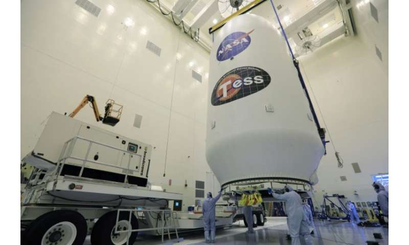 The SpaceX payload fairing containing the NASA's Transiting Exoplanet Survey Satellite (TESS) is moved by crane to a transporter