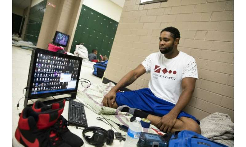"Tony Winborne, 37, looks at a computer in a Hurricane Florence evacuation shelter where, he says, it's ""better safe than so"
