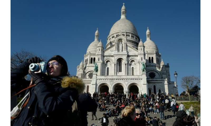 Tourists throng the steps outside the Sacre Coeur basilica in Paris' iconic Montmartre district, an area at risk of being swampe