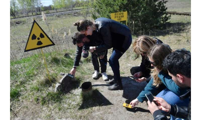 Tourists use Geiger counters to measure the level of radioactivity in the area