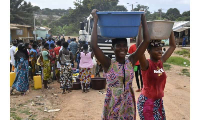 Young Ivorian women carrying precious water in the city where the taps have run dry