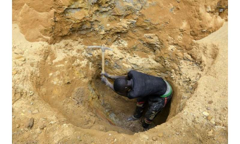 Young men dig with pickaxes in the hope of finding gold in the Cameroon town of Betare Oya