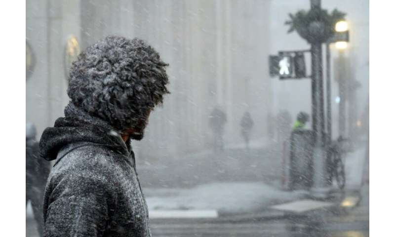 A man waits to cross a street in downtown Manhattan during a snow storm