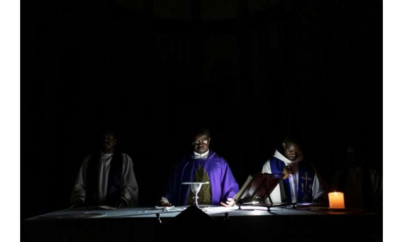 A priest prays during a service at the Ponta Gea Roman Catholic Cathedral