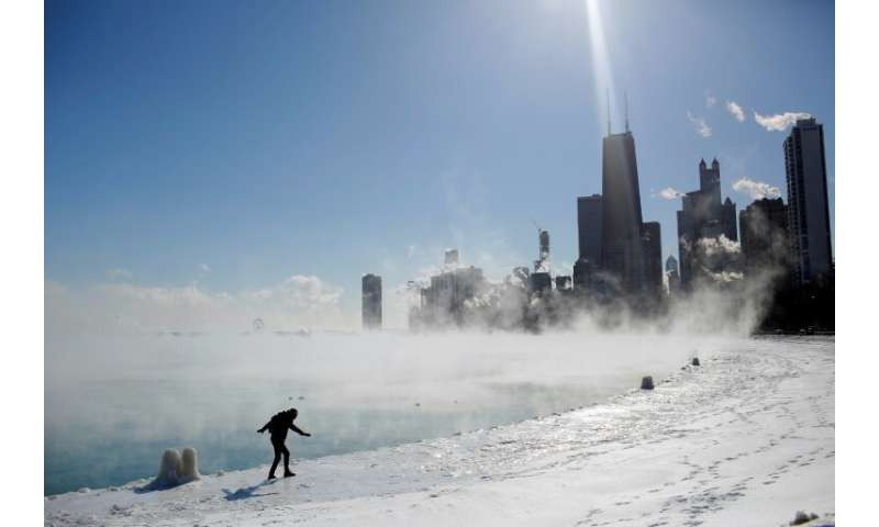 Marius Radoi keeps his balance as he walks on the edge of Lake Michigan's shore line as temperatures dropped to -20 degrees F (-