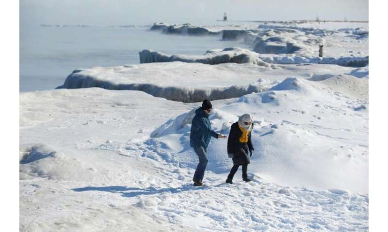 People walk along Lake Michigan's frozen shoreline as temperatures dropped to -20 degrees F (-29C) Chicago