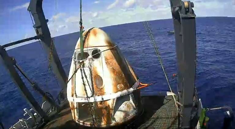 This still image taken from NASA TV shows SpaceX's Crew Dragon spacecraft safely aboard the company's recovery vessel following