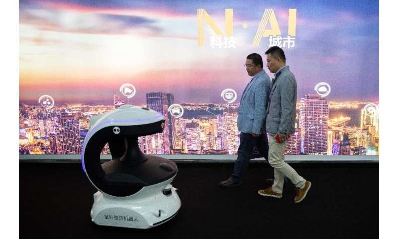 Visitors walk past a security robot named APV3 with a facial recognition system at the 14th China International Exhibition on Pu