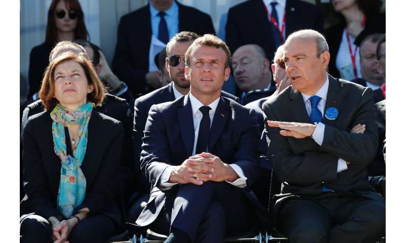 French President Emmanuel Macron sits between Defence Minister Florence Parly, left, and Dassault Aviation chief executive Eric