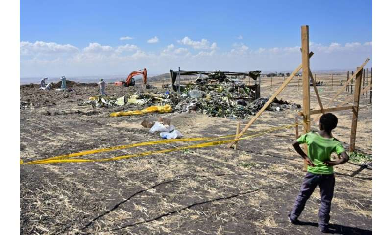 A boy looks on as forensic investigators work at the crash site of an Ethiopian Airlines Boeing 737 MAX aircraft
