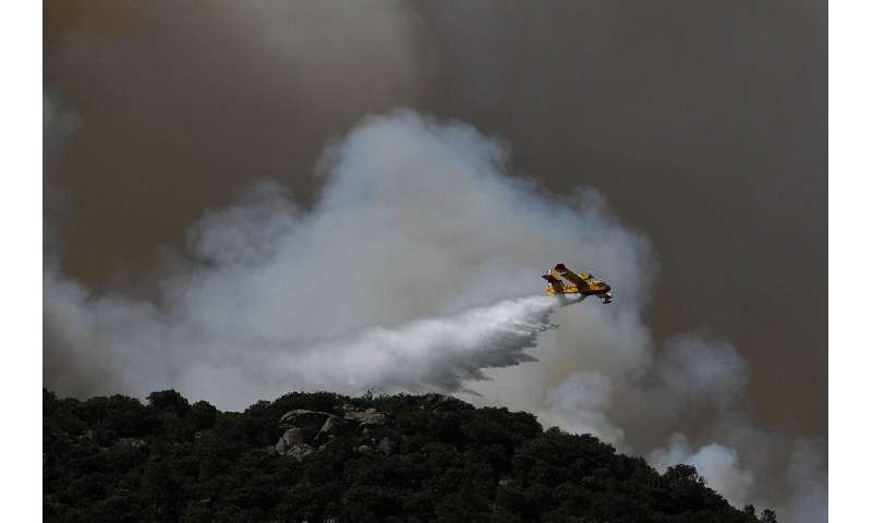 A Canadair drops water over a wildfire in the outskirts of Cenicientos in central Spain as Spain was hit by more wildfires amid