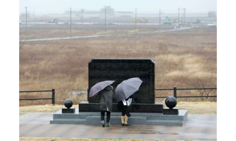 A couple prays in front of a memorial monument in Namie, Fukushima Prefecture, on the eighth anniversary of the 2011 tsunami dis