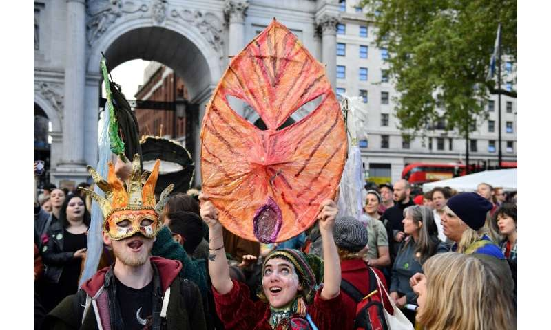 Activists sing songs in London on April 25, 2019 during the Extinction Rebellion group's protest calling for political efforts t